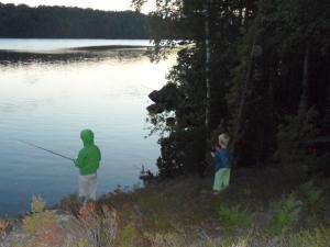 Fiske på klippa i solnedgång