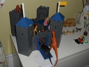 Dinosarna undersöker nyfiket borgen. Den evigt vrålande T-rexen ryter hotfullt från ett torn, medan en fé gör kraftfullt motstånd. De flesta riddarna har fallit.